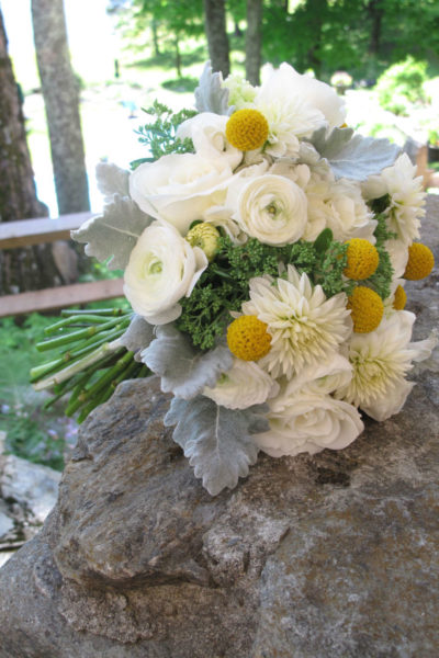 white and yellow bouquet posed on a rock