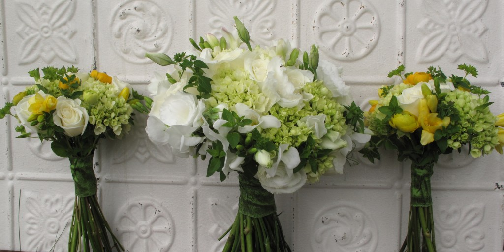 photo of 3 wedding bouquets lined up against a white tin background