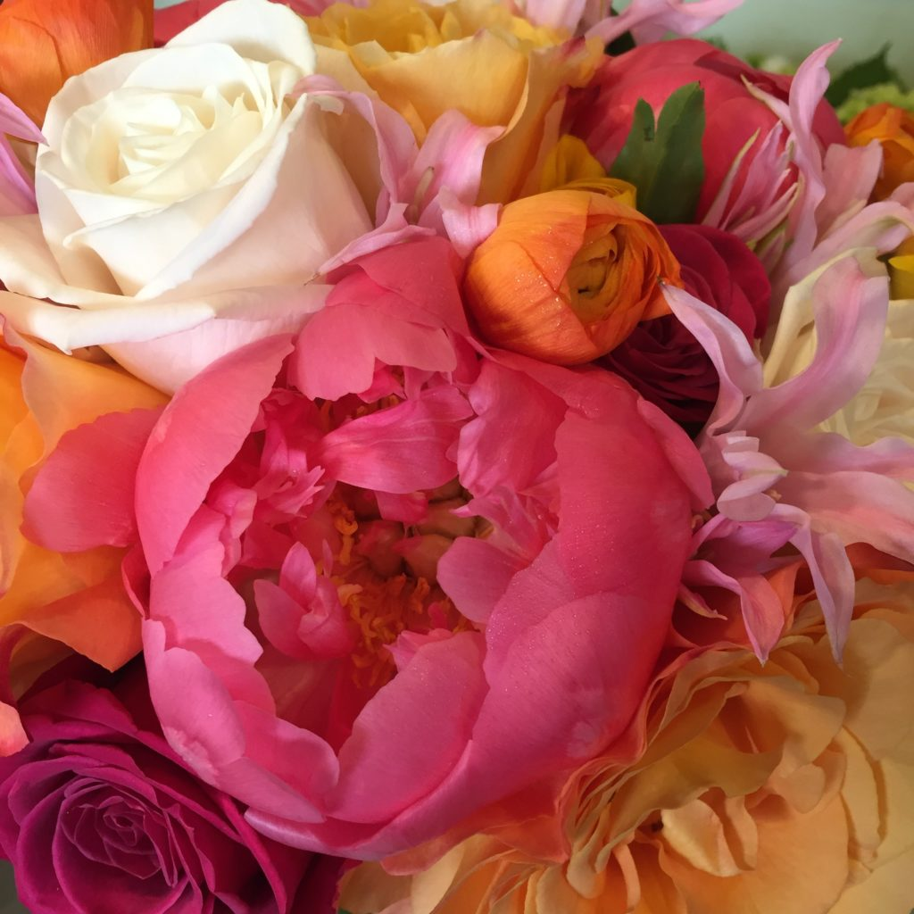 Coral peony, orange ranunculus and roses